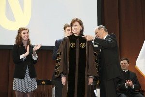 Riordan accepts the symbols of the office, the President's Medallion and a University hood in the school's colors of brown and gold.