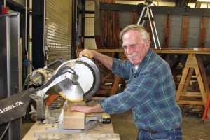Ida May Project Manager Edward Peterson at home with a saw, cutting a board to size.