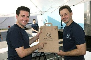 Our Harvest co-founders Scott Reich (left), and Mike Winick point to a bag sporting the company's logo.