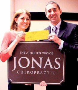Dr. Jonathan DeGorter of Jonas Chiropractic & Sports Injury Care presents the sponsorship check to Race Director Karen Schackner.
